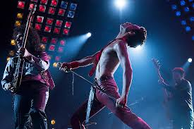 Queen band members Brian May, Freddie Mercury, and John Deacon   (from left to right) performing on stage during a show.  Photo courtesy of The New York Times.