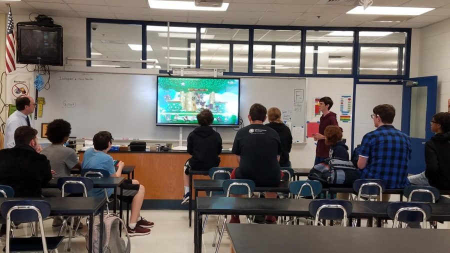A+group+of+students+participate+in+a+Super+Smash+Bros+tournament+on+a+new+interactive+whiteboard.%0A