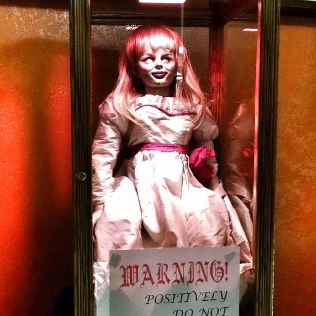 A+replica+Annabelle+doll+in+a+special+transparent+enclosure.+A+sign+is+propped+up+that+says+%0A+Warning%21+Positively+Do+Not.+Photo+courtesy+of+Flickr.