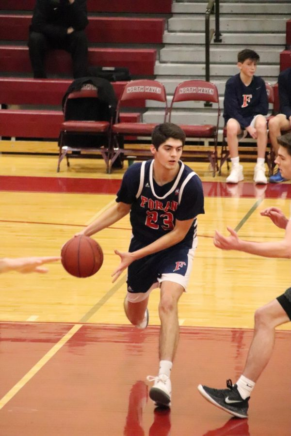 John Shannon takes the ball up the court. Shannon led Foran with 22 of their 61 points. Photo courtesy of Corina Massey.