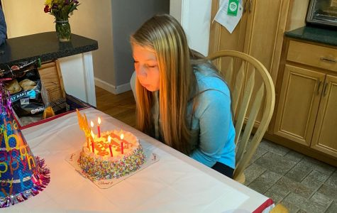 Sam Lavallee, freshman, putting out the candles on her birthday cake in the comfort of her home.
