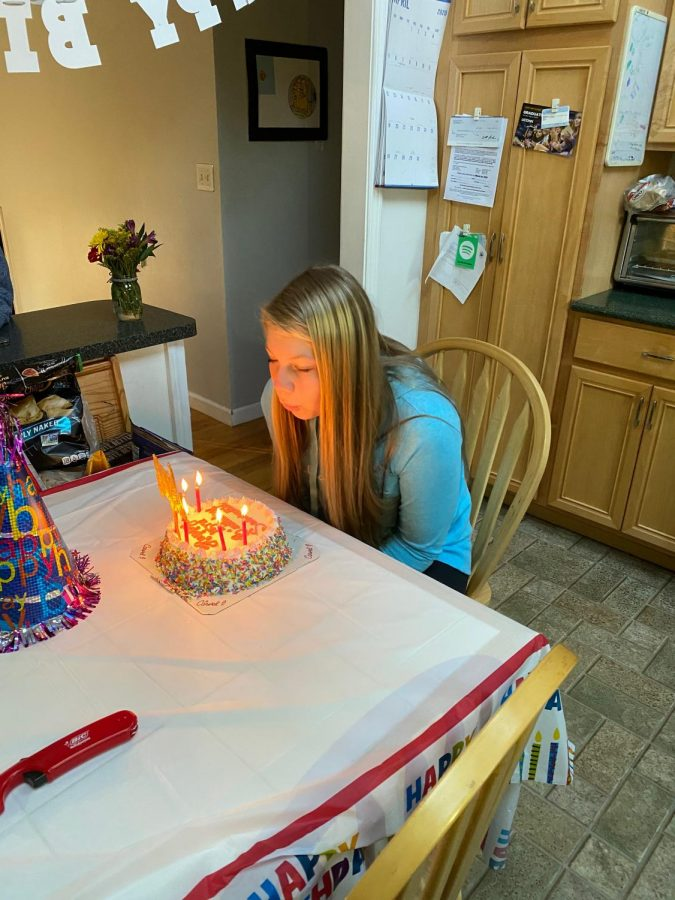 Sam+Lavallee%2C+freshman%2C+putting+out+the+candles+on+her+birthday+cake+in+the+comfort+of+her+home.%0A