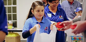 Giving Back at a Young Age: A young volunteer helps fill food bags.  Photo courtesy of: Food 2 Kids Website
