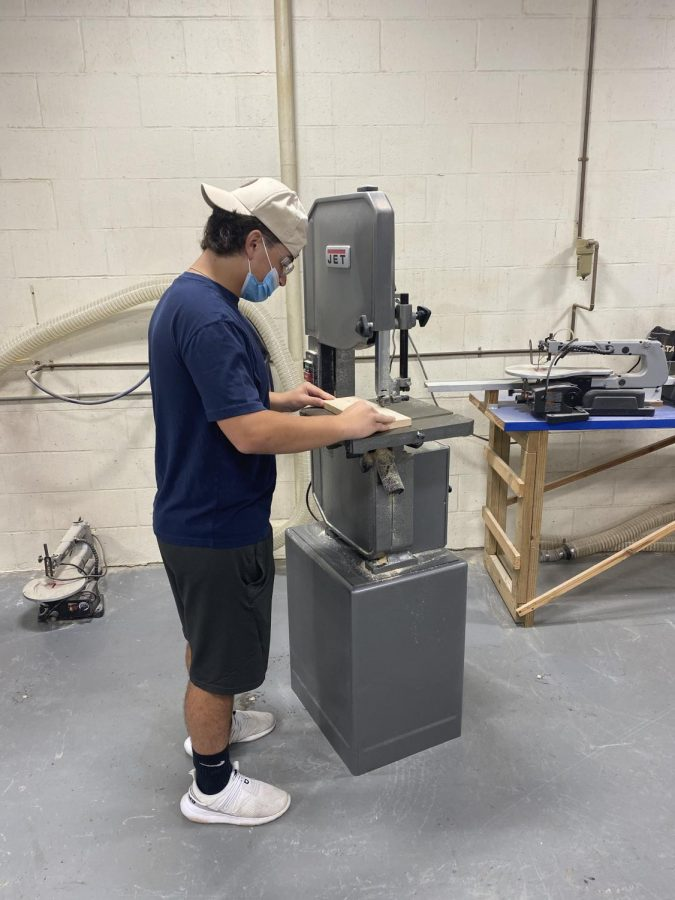 Perfecting their craft: Freshman Nolan Fortier in Wood Tech working with the band saw.