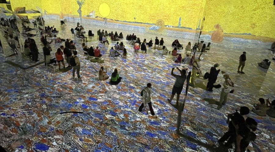 """A Unique View: People watch Van Gogh's """"The Sower"""" projected on the walls and floor of the Immersive Van Gogh Exhibit in New York. Photo courtesy: Maria Garbin, July 31, 2021."""